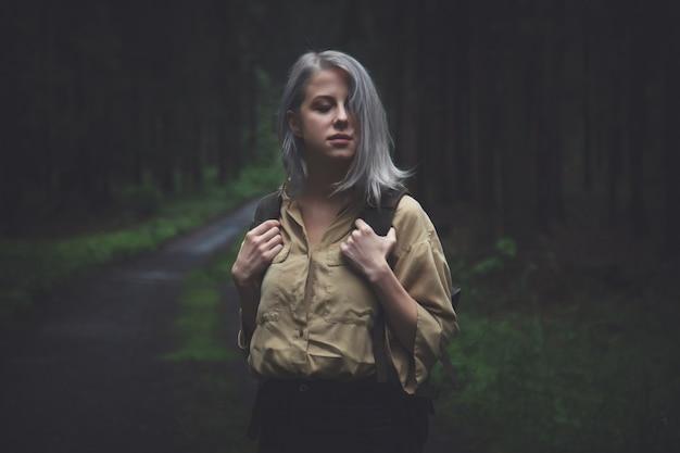 Blondevrouw met rugzak in regenachtige dag in bos