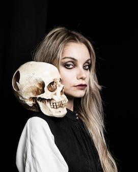 Blondevrouw met schedel op schouder