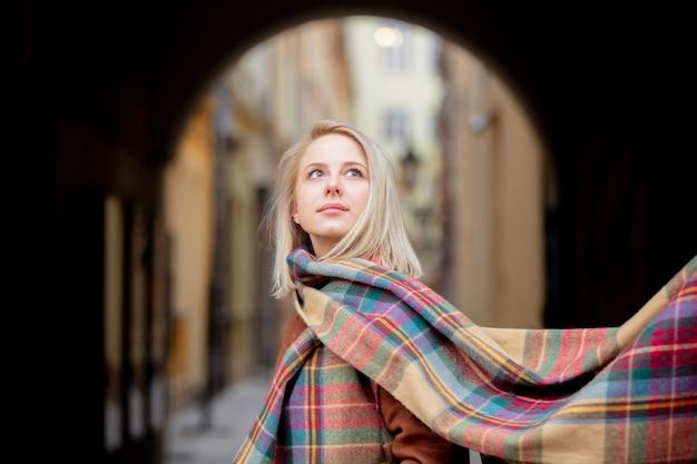 Blondevrouw met sjaal in oude stad van wroclaw