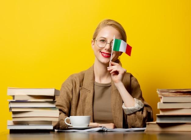 Blondevrouw met vlag van italië en boeken op geel