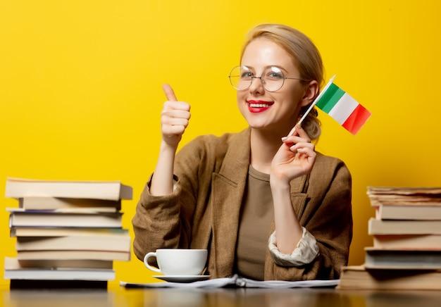 Blondevrouw met vlag van italië en boeken op geel Premium Foto
