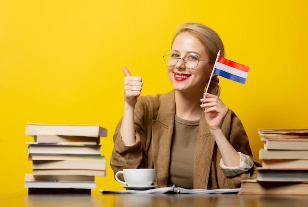 Blondevrouw met vlag van nederland en boeken over geel