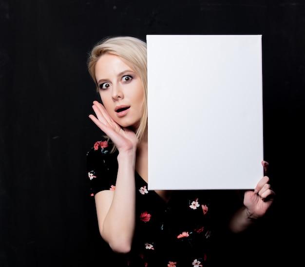 Blondevrouw met wit bord op donkere muur