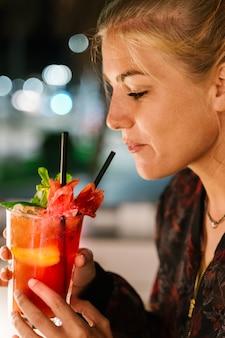 Blondevrouw ongeveer om een rode cocktail met een stro bij nacht te drinken