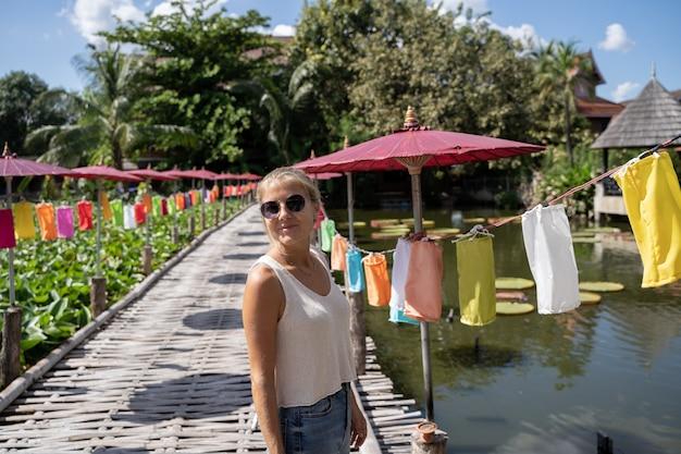 Blondevrouw op een houten brug die een vijver met gekleurde paraplu's onder ogen zien
