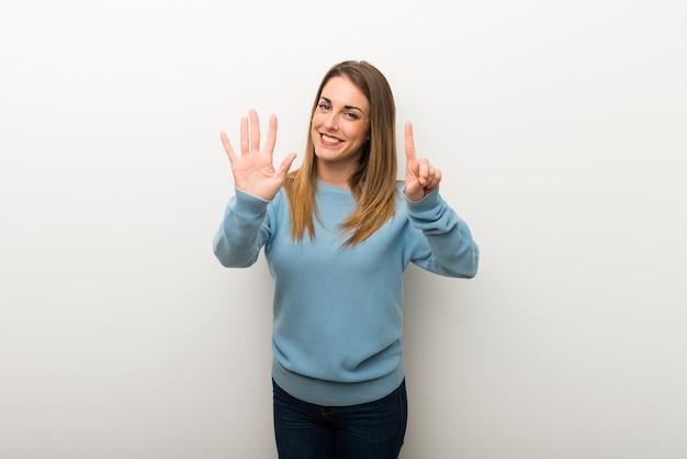 Blondevrouw op geïsoleerd wit die zes met vingers tellen