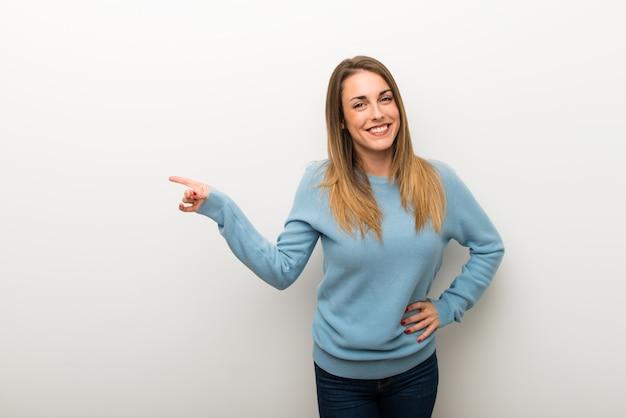 Blondevrouw op geïsoleerde witte achtergrond die vinger aan de kant richten en een product voorstellen