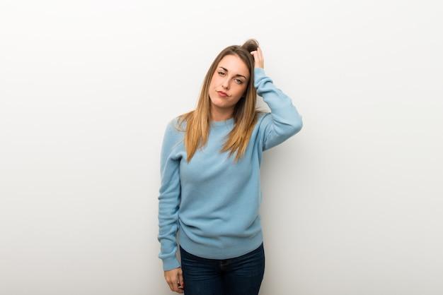 Blondevrouw op geïsoleerde witte achtergrond met een uitdrukking van frustratie en begrip niet