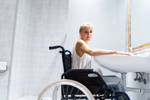 Blondevrouwenzitting in een rolstoel voor een gootsteen in een badkamers