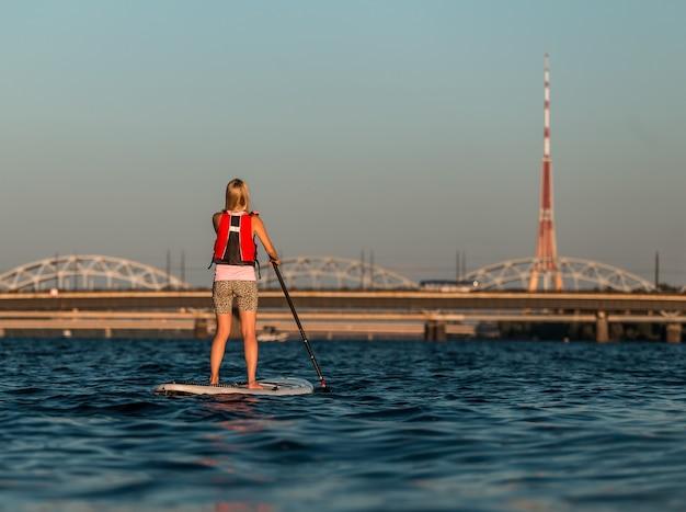 Blondewijfje op paddleboard op daugava-rivier, letland