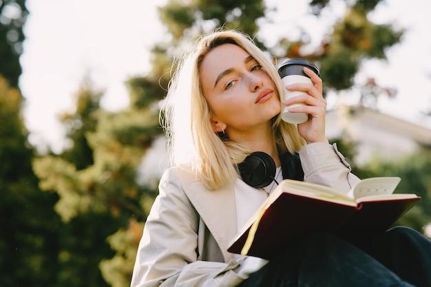 Blondezitting op een gras met hoofdtelefoons