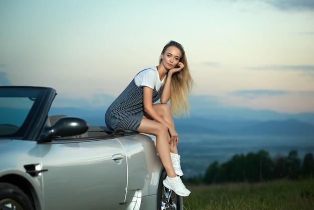 Blondezitting op luxueuze zilveren cabriolet en het stellen.