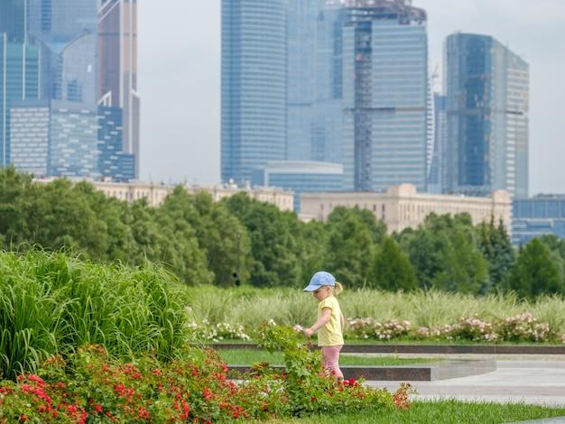 Blondharige meisjesbaby bewondert de bloemen tegen de achtergrond van wolkenkrabbers