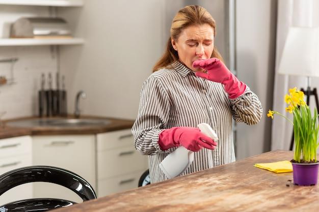 Blondharige rijpe huisvrouw die de keuken schoonmaakt en niest terwijl ze allergisch is