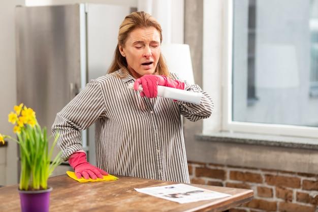 Blondharige vrouw die de tafel schoonmaakt en niest terwijl ze allergisch is voor stof