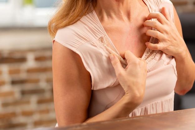 Blondharige vrouw met roodheid op haar borst vanwege allergie