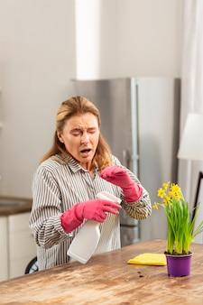 Blondharige zakenvrouw die in het weekend de keuken schoonmaakt en niest terwijl ze allergisch is