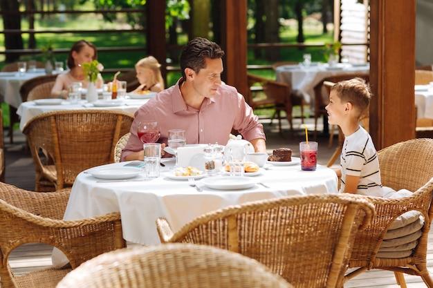 Blondharige zoon. schattige blonde-haired zoon gestreept shirt dragen ontbijten met zijn zorgzame liefdevolle vader