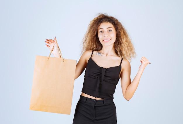 Blondie meisje houdt een kartonnen boodschappentas vast en wijst naar ergens anders.