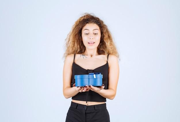 Blondie meisje met een blauwe geschenkdoos en kijkt verrast.