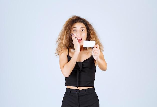 Blondie meisje met een visitekaartje en kijkt verrast.