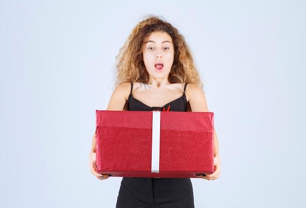 Blondie meisje met krullende haren houdt een rode geschenkdoos vast en kijkt verrast.