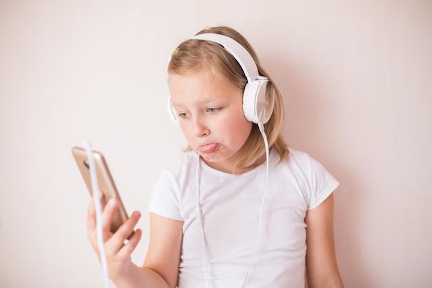 Blondie tienermeisje dat met oortelefoons aan muziek luistert