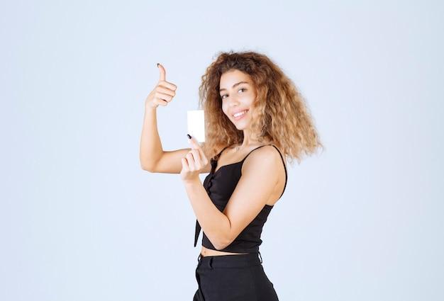 Blondiemeisje met een adreskaartje dat plezierteken toont.