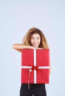 Blondiemeisje met krullende haren die een rode geschenkdoos vasthouden en zich positief voelen.