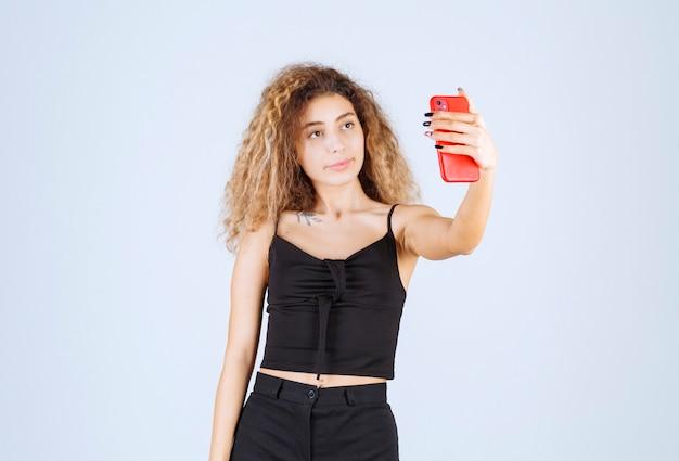 Blondiemeisje met krullende haren die haar selfie nemen.