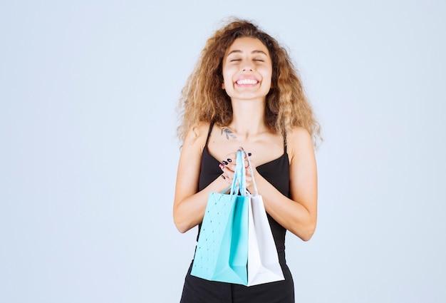 Blondiemeisje met krullende haren die tevreden haar kleurrijke boodschappentassen vasthoudt.