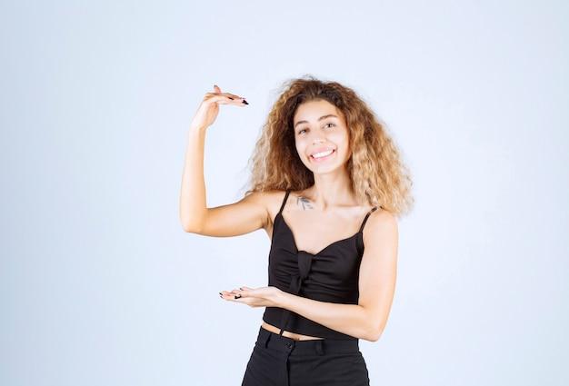 Blondievrouw die de grootte van een voorwerp toont.