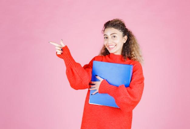 Blondievrouw in rood sweatshirt die ergens aan de linkerkant wijst.
