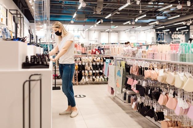 Blondje in wit t-shirt en spijkerbroek gebruikt een beschermend masker bij het betalen van goederen bij het afrekenen
