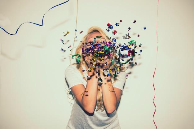 Blondjes blazen confetti en verbergt haar gezicht