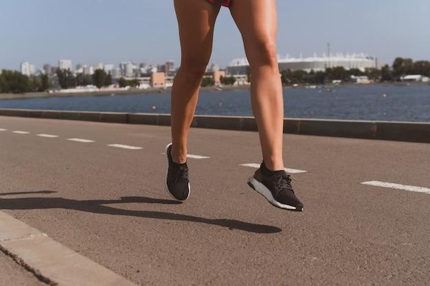 Blondy sportieve vrouw met lang haar loopt in het stadion