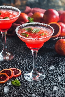 Blood orange margarita cocktail met munt en rode sinaasappel in zout omrand cocktailglas