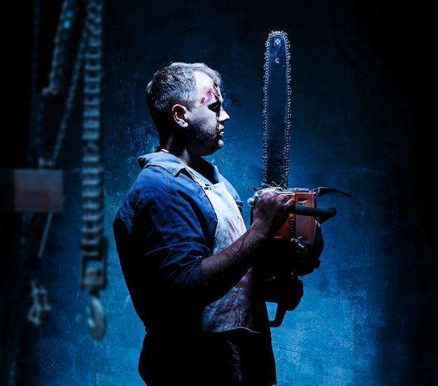 Bloody halloween-thema: gekke moordenaar als bloedige slager met elektrische zaag op donkerblauwe achtergrond