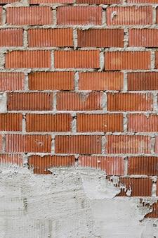 Blootgestelde bakstenen muur met gips