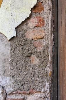 Blootgestelde bakstenen muur met peeling betonnen oppervlak