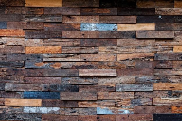 Blootgestelde houten muur aan de buitenkant, lappendeken van ruw hout dat een prachtig parket houtpatroon vormt, houten muurpatroon