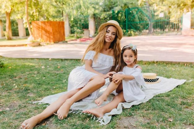 Blootsvoets langharige meisje ontspannen op een deken met zusje en zonnebaden in zonnige dag. openluchtportret van glimlachende jonge vrouw die op het gras met leuke dochter in elegante kleding koelen.