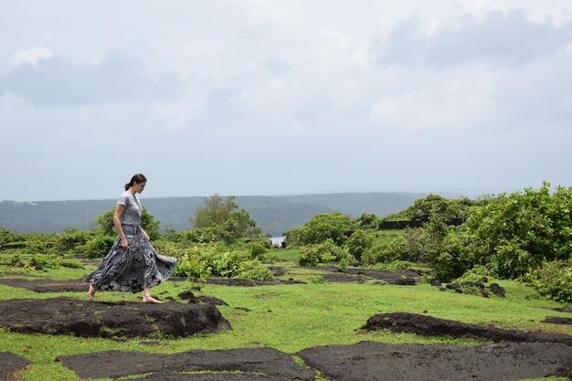 Blootsvoets meisje in een lange rok die op grote stenen springt