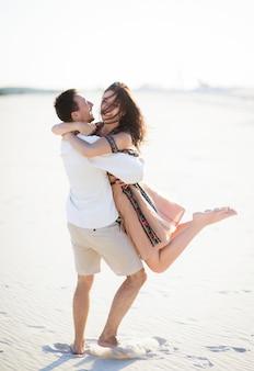 Blootsvoets paar in lichte geborduurde kleding loopt op een wit zand