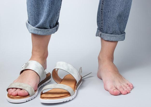 Blootsvoets vrouwelijk been en geschoeid in sandaal op wit