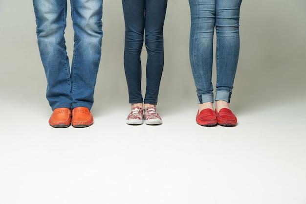 Blootvoetse benen van moeder, vader en klein kind die jeans dragen die op witte achtergrond worden geïsoleerd
