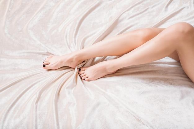 Blote benen van een vrouw die in bed ligt