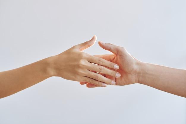 Blote handen van twee onherkenbare mensen die naar elkaar reiken