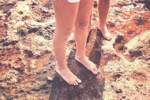 Blote mannelijke en vrouwelijke benen staan op een natte steen.