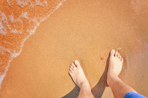 Blote mannelijke voeten op kustwandeling langs oceaanstrand zomervakantie reizen en reizen naar warme landen...